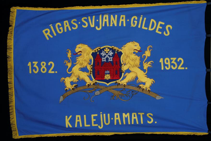 Rīgas Sv. Jāņa ģildes Kalēju amata karogs ar mākslinieka K.Brencēna veidoto ģērboni, 1933. g.
